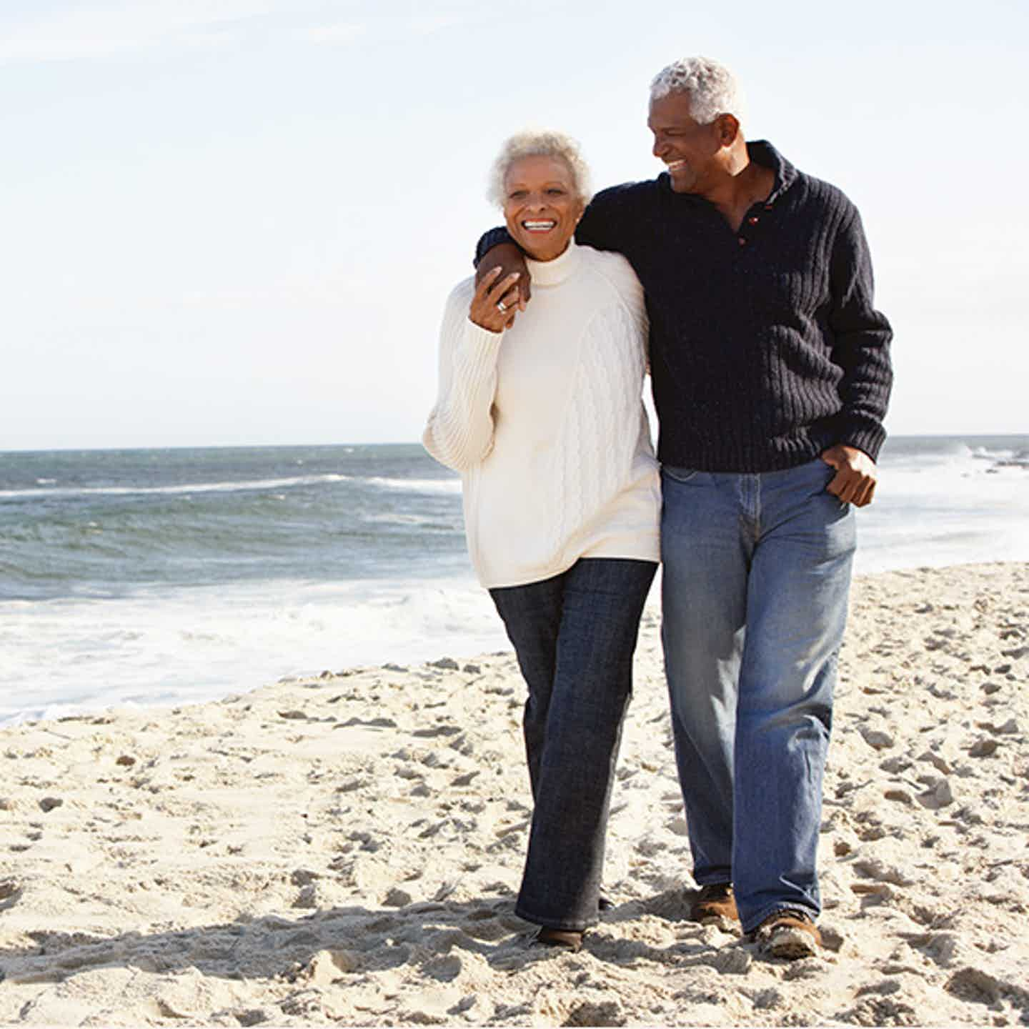 Mature couple walking on the beach discusing cancer prevention