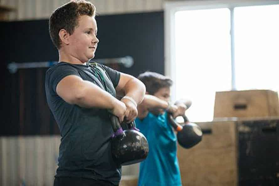 Kids lifting kettlebells to test muscular strength