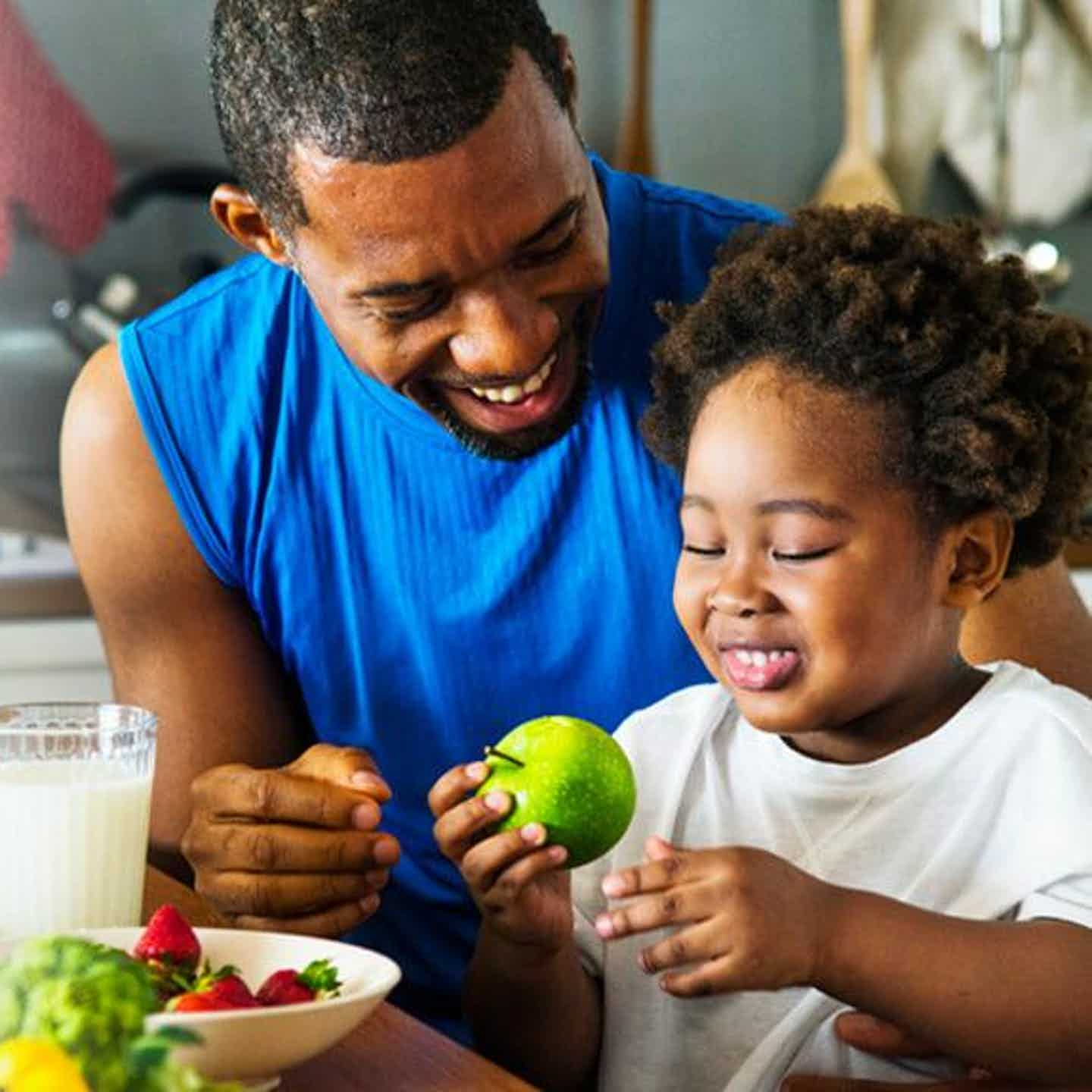 Dad and daughter eating fruit as part of healthy living